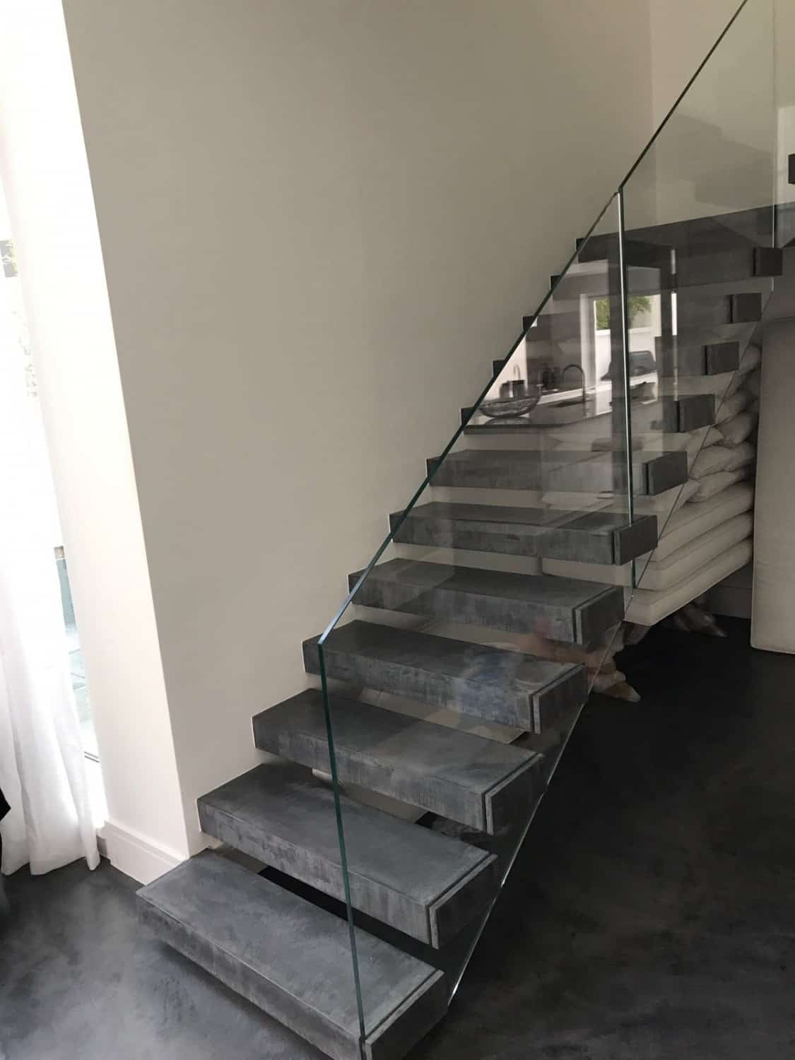 Concrete floor stair case with glass sides