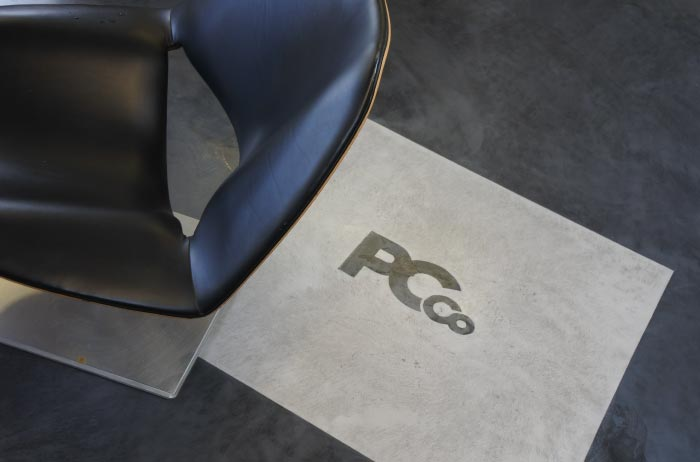 Close-up of Polished Concrete logo inlayed in the showroom floor.
