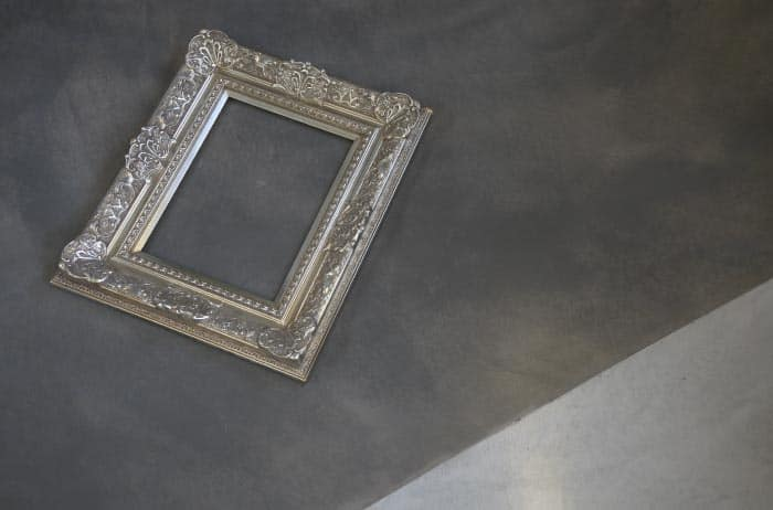 Ornate picture frame laid on the polished concrete showroom floor.