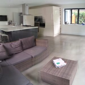 Open plan living room and kitchen with polished concrete floor